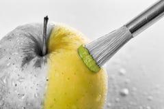 Grüne Apfelnahaufnahme mit den Wassertropfen, die auf einem weißen b gemalt werden Stockfotografie