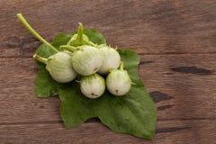 Grüne Aubergine mit Wassertropfen und Aubergine verlässt auf hölzernem Lizenzfreie Stockfotografie