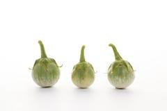 Grüne Aubergine mit Wassertropfen und Aubergine verlässt auf Weiß Stockfotos