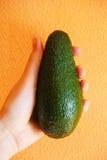 Grüne Avocado in der Hand auf einem orange Hintergrund Lizenzfreies Stockfoto