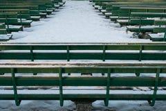 Grüne Bänke im Winterpark Stockfotografie