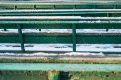 Grüne Bänke im Winterpark Stockbilder