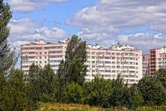 Grüne Büsche und Bäume vor einem Block von mehrstöckigen Wohngebäuden Stockbilder