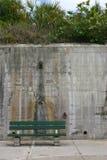 Grüne Bank eingestellt gegen eine hohe Betonmauer Stockbilder