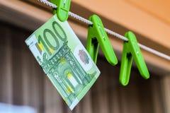 Grüne Banknote in einem grünen Kleiderhaken Lizenzfreies Stockfoto