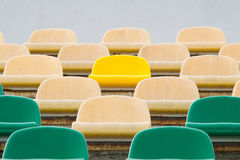 Grüne, beige und gelbe Sitze in altem geöffnetem Stadion 1 Stockfoto
