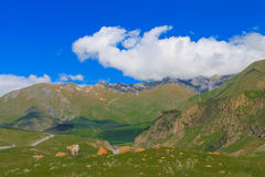 grüne Berge mit Gletschern unter Wolken nahe der Straße Lizenzfreie Stockbilder