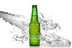 Grüne Bierflasche mit Wasserspritzen Lizenzfreie Stockbilder