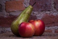 Grüne Birne und roter Apfel auf einer Hintergrundwand Stockfotos