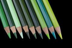9 grüne Bleistifte - schwarzer Hintergrund Lizenzfreie Stockfotos