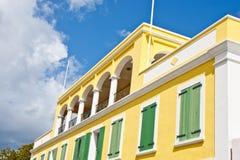 Grüne Blendenverschlüsse auf gelbem Gebäude unter blauem Himmel Lizenzfreie Stockbilder