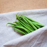 Grüne Bohnen auf einer Tabelle mit einer Serviette lizenzfreie stockfotos