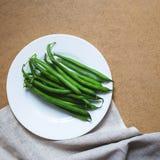 Grüne Bohnen auf einer weißen Platte lizenzfreies stockfoto