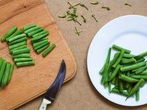 Grüne Bohnen auf einer weißen Platte auf einer Tabelle mit einem Messer Lizenzfreie Stockbilder