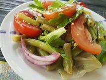 Grüne Bohnen des Kopfsalates, Tomate, auf einem hölzernen Hintergrund Lizenzfreies Stockfoto