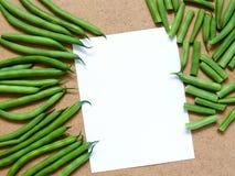 Grüne Bohnen und geschnittene grüne Bohnen auf dem Tisch mit einem Weiß lizenzfreie stockfotos