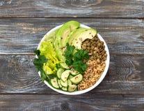 Grüne Buddha-Schüssel mit Linsen, Quinoa, Avocado, Gurke, frischem Kopfsalat, Kräutern und Samen Stockbild