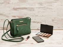 Grüne Damen Handtasche, Telefon, Lidschattenpalette und ein Lippenstift auf einem hölzernen Hintergrund lizenzfreie stockbilder