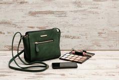 Grüne Damen Handtasche, Telefon, Lidschattenpalette und ein Lippenstift auf einem hölzernen Hintergrund Art und Weisekonzept lizenzfreie stockfotografie