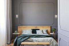 Grüne Decke auf hölzernem Bett mit Kissen in grauem Schlafzimmer interio lizenzfreie stockfotografie