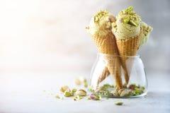 Grüne Eiscreme im Waffelkegel mit Schokolade und Pistazien auf grauem Steinhintergrund Sommerlebensmittelkonzept, Kopie lizenzfreie stockfotos