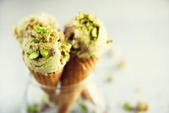 Grüne Eiscreme im Waffelkegel mit Schokolade und Pistazien auf grauem Steinhintergrund Sommerlebensmittelkonzept, Kopie lizenzfreie stockbilder