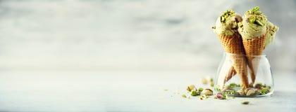 Grüne Eiscreme im Waffelkegel mit Schokolade und Pistazien auf grauem Steinhintergrund Sommerlebensmittelkonzept, Kopie stockfoto