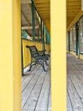 Grüne Eisen-Bank auf einem hölzernen Portal eines gelben Gebäudes Stockfotos