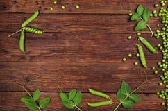 Grüne Erbsen auf alter Draufsicht des Holztischs stockbilder