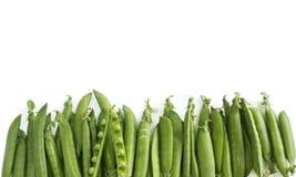 Grüne Erbsen auf einem weißen Hintergrund Grüne Erbsen an der Grenze des Bildes mit Kopienraum für Text Lizenzfreies Stockfoto