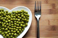 Grüne Erbsen auf Herz-förmiger Platte Lizenzfreies Stockfoto