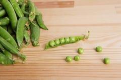Grüne Erbsen in den Hülsen wählten frisch auf Holz aus Lizenzfreie Stockbilder