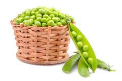 grüne Erbsen in einem Weidenkorb auf einem weißen Hintergrund Getrennt stockfoto