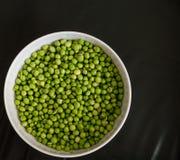 Grüne Erbsen in einer weißen Schüssel Stockfoto