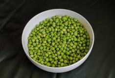 Grüne Erbsen in einer weißen Schüssel Lizenzfreie Stockfotografie