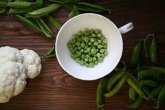 Grüne Erbsen und Blumenkohl lizenzfreie stockbilder