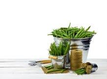 Grüne Erbsen und Gartenwerkzeuge lokalisiert auf einem weißen Hintergrund witho lizenzfreies stockfoto
