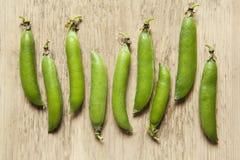 Grüne Erbsenhülsen auf einem hölzernen Hintergrund Lizenzfreie Stockbilder