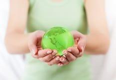 Grüne Erdkugel in den menschlichen Händen Stockbild