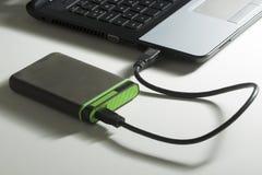Grüne externe Festplatte mit Kabel auf Weiß Stockfotografie