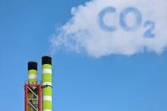 Grüne Fabrikrohre mit CO2-Emission stockbilder