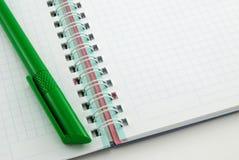 Grüne Feder im Notizbuch mit Ringen Stockfotos