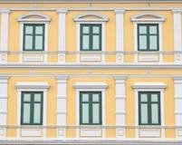 Grüne Fenster auf orange Wand Stockfotos