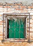 Grüne Fensterläden blockieren Fenster hinter verrostetem Grill auf unfertigem Br Lizenzfreie Stockbilder