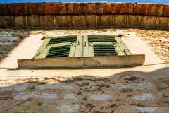 Grüne Fensterläden geschlossene Fenster gegen eine verwitterte braune Wand in Eze, Frankreich lizenzfreie stockfotografie