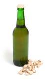 Grüne Flasche und Pistazien Stockfotografie