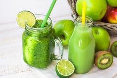 Grüne Frucht und Krautsaft in der Flasche, Gemüsesmoothie im Glasbecher draußen Sommerfrühlings-Sonnenlichtstellen Lizenzfreies Stockfoto