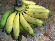 Grüne gelbe Banane auf der Marmortabelle Stockfotos