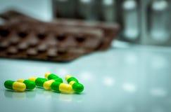 Grüne, gelbe tramadol Kapselpillen auf unscharfem Blisterpackungs-BAC Stockbilder
