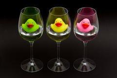 Grüne, gelbe und rosafarbene Gummienten in den Weingläsern stockbild